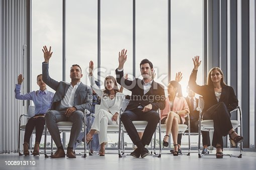 istock Group of business people raise hands up to agree with speaker in the meeting room 1008913110