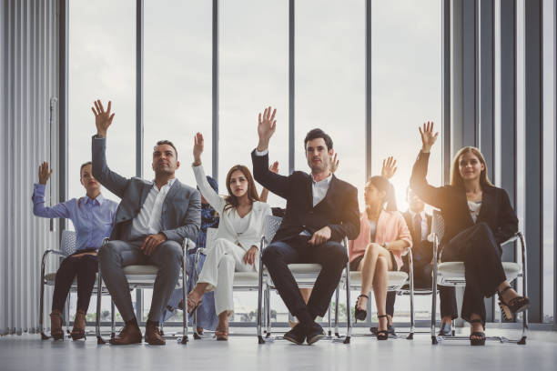 group of business people raise hands up to agree with speaker in the meeting room - training imagens e fotografias de stock