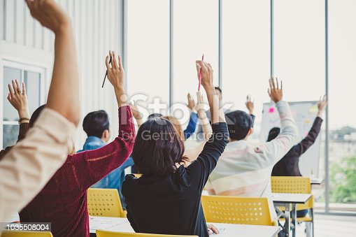 istock Group of business people raise hands up to agree with speaker in the meeting room seminar 1035508004