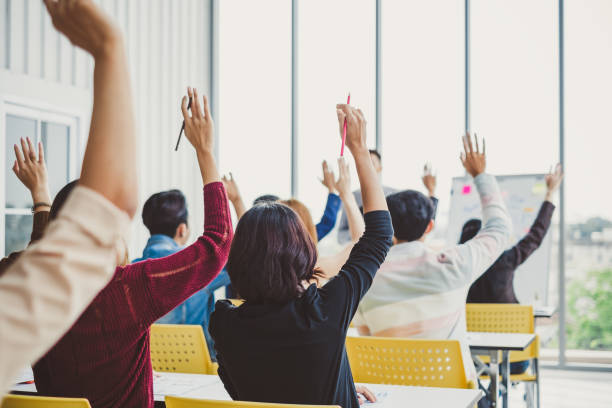 group of business people raise hands up to agree with speaker in the meeting room seminar - демократия стоковые фото и изображения