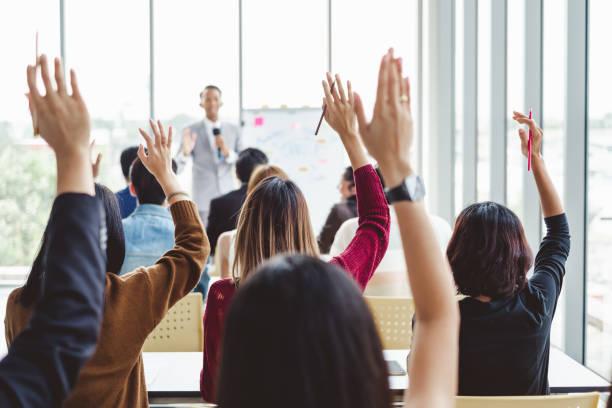 groep van mensen uit het bedrijfsleven doen opstaan handen eens met de spreker in de vergadering ruimte seminar - voting hands stockfoto's en -beelden