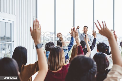 istock Group of business people raise hands up to agree with speaker in the meeting room seminar 1056862092