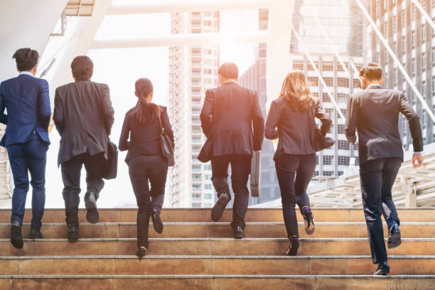 Group of Business People Running in Row Lively business team running in the city. Group of businessmen and businesswomen. Teamwork, togetherness, liveliness, business concept. agility stock pictures, royalty-free photos & images