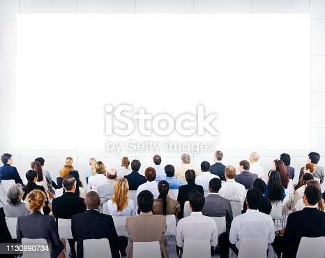 Group of business people sitting and looking at the blank presenation.