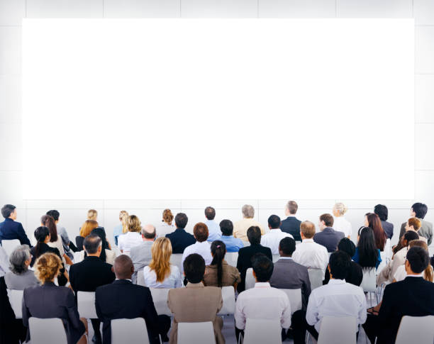 Group of business people sitting and looking at the blank presenation. stock photo