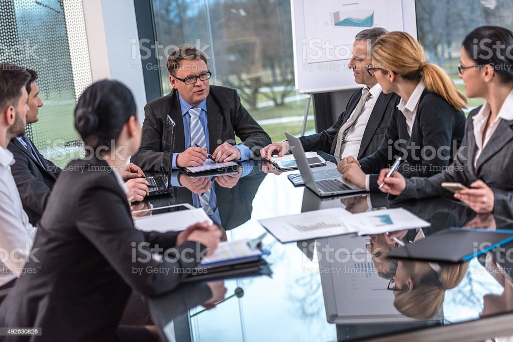 Group of business people sitting at a table discussing project stock photo