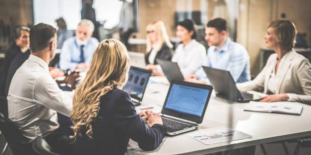 Gruppe von Geschäftsleuten mit Laptops eine Diskussion an einem Tisch sitzen – Foto