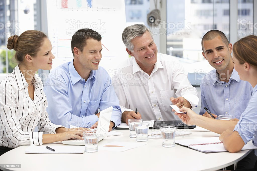 Group of business people sitting in a meeting stock photo