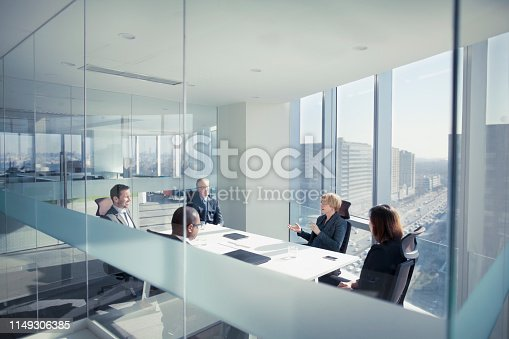Group of business people team sitting together in conference meeting room in contemporary modern office bright sunny daylight talking discussing planning organizing strategy well dressed suit and tie teamwork cooperation diversity multi-ethnic problems solutions unity cityscape downtown urban leader boss CEO executive