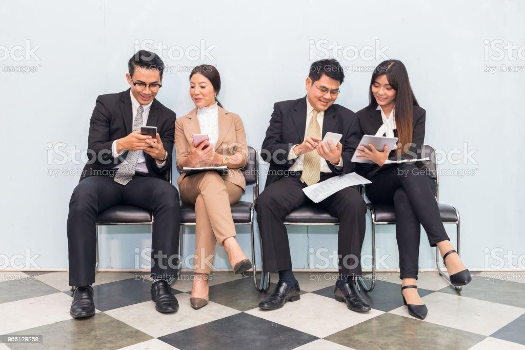 Grupp av affärsmän som använder enheten i paus - Royaltyfri Affärsmänniska Bildbanksbilder