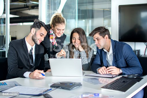 istock Group of business people using laptop together in the office. 648046560