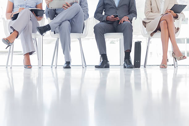 Group of business people waiting Group of business people waiting together in a waiting room cross legged stock pictures, royalty-free photos & images