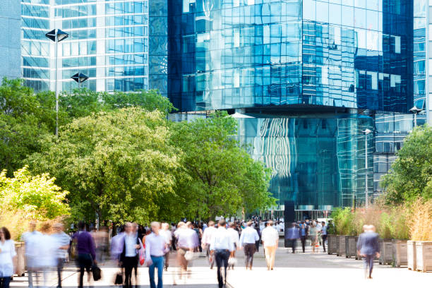 Group of Business People Walking Toward Office Building Entrance, La Defense, Paris, France Crowd of  motion blurred business people walking through financial district, modern blue glass office buildings are visible in the background, summer sunny day, La Defense, Paris, France. central europe stock pictures, royalty-free photos & images