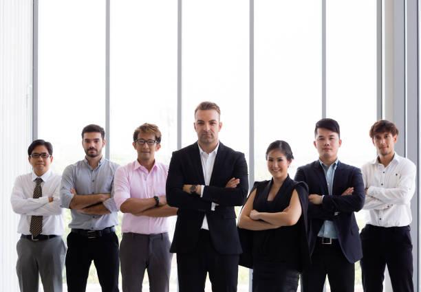 Gruppe von Geschäftsleuten mit Waffen im Amt gekreuzt – Foto