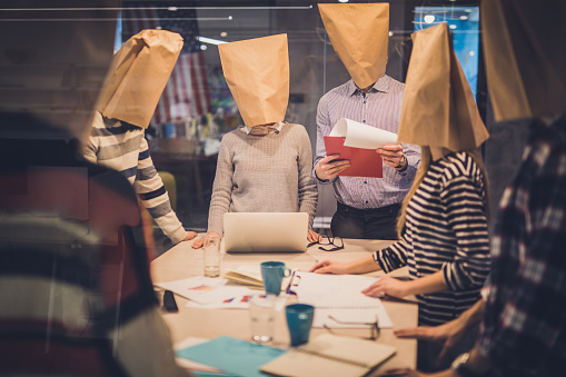 istock Group of business people with paper bags having a meeting in the office. 911979044