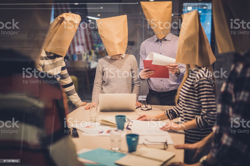Group of business people with paper bags having a meeting in the office. stock photo