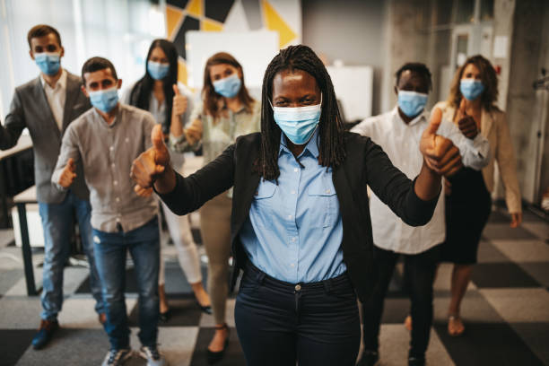 Group of business people with protective face masks celebrating success stock photo