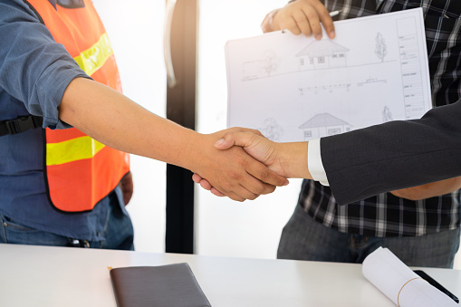 912867216 istock photo Group of business peoples shaking hands after successful building construction planning project at meeting.Successful deal after meeting. 968377540
