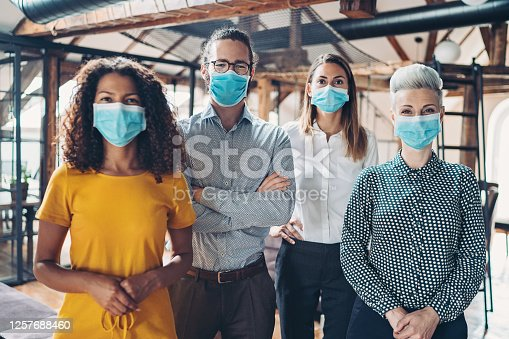Business persons with protective masks standing side by side