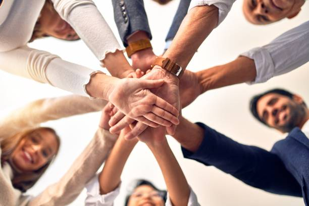 Group of business workers standing with hands together at the office stock photo