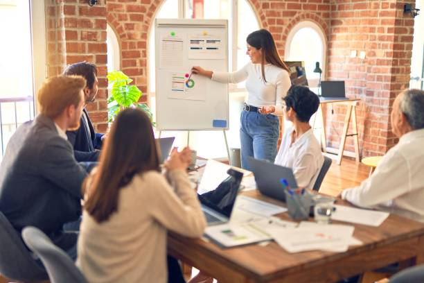 Group of business workers working together in a meeting. One of them making presentation to colleagues at the office stock photo