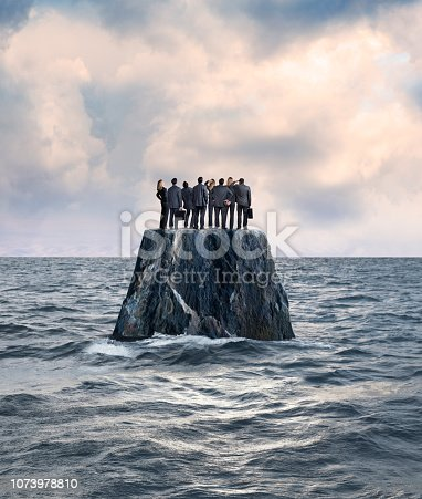 A group of businessmen and businesswomen stand side by side on top of a rocky island that sits in the middle of the ocean.