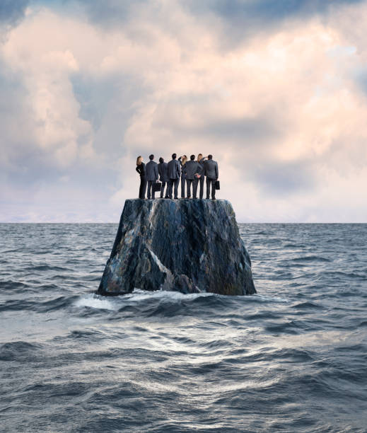 Group Of Businessman And Businesswoman Stand On Isolated Island In Ocean A group of businessmen and businesswomen stand side by side on top of a rocky island that sits in the middle of the ocean. aground stock pictures, royalty-free photos & images