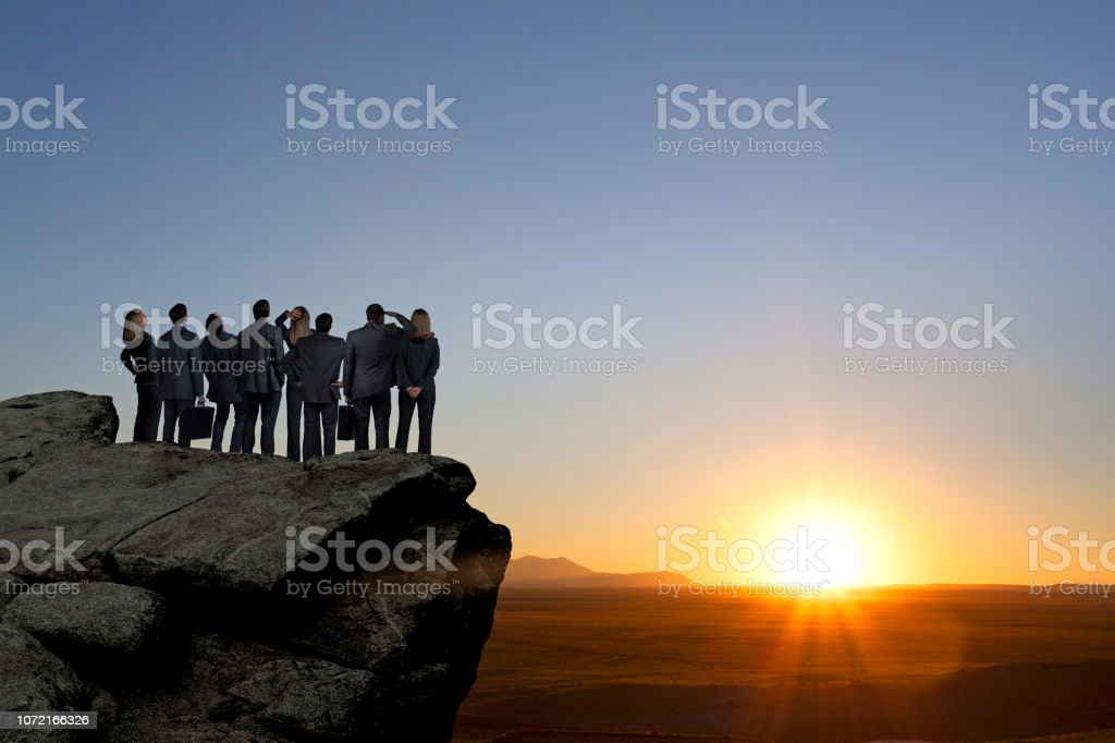 Group Of Businessmen And Businesswomen Stand On Promontory Looking Out Towards Sunset stock photo