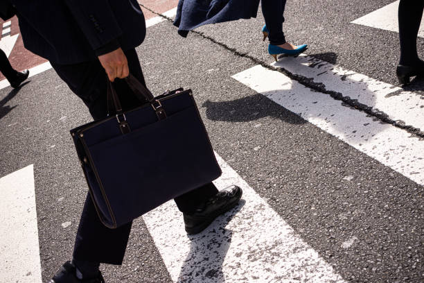 Group of businessmen and women walk along crosswalk in Shinjuku, Tokyo, Japan stock photo