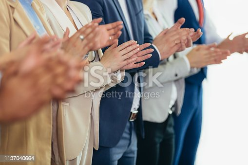 1031822210 istock photo Group of businesspeople clapping in office. 1137040664