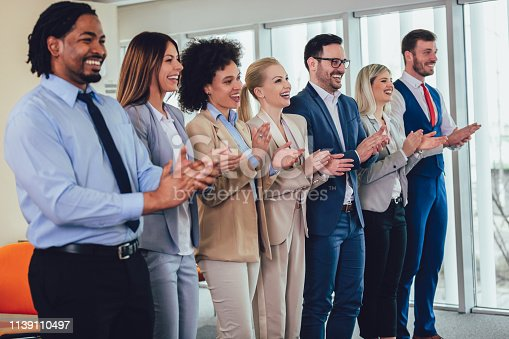 1031822210 istock photo Group of businesspeople clapping in office. 1139110497