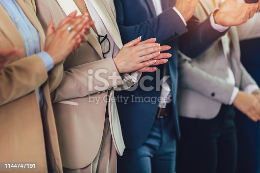 1031822210 istock photo Group of businesspeople clapping in office. 1144747191