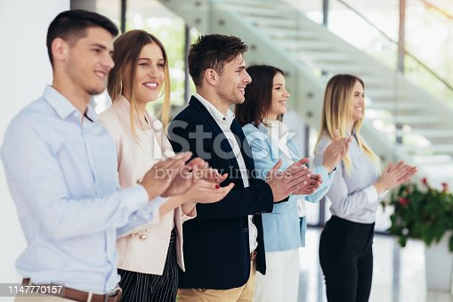 1031822210 istock photo Group of businesspeople clapping in office. 1147770157