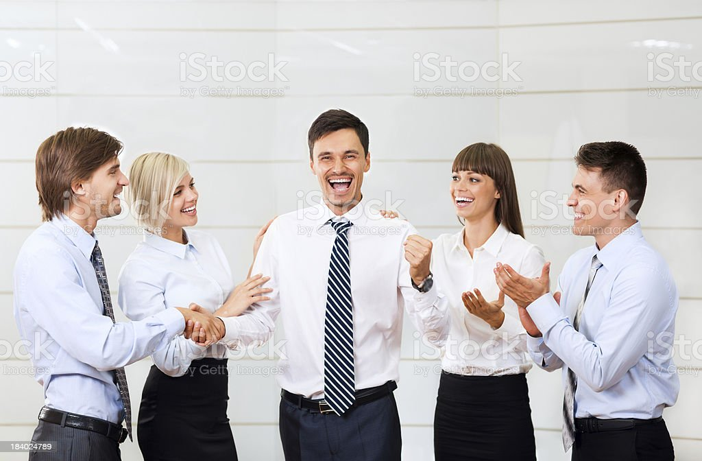 Group of businesspeople congratulating their leader stock photo