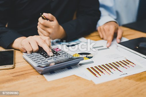975599364istockphoto Group of Businesspeople discussing the charts and graphs,businessmen discussing on stockmarket document in office,Business partners consult documents at meeting,Concept of brainstorm teamwork planning 975599060