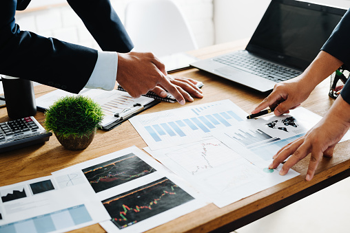 istock Group of Businesspeople discussing the charts and graphs,businessmen discussing on stockmarket document in office,Business partners consult documents at meeting,Concept of brainstorm teamwork planning 975599364