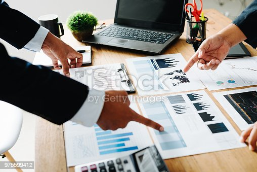 975599364istockphoto Group of Businesspeople discussing the charts and graphs,businessmen discussing on stockmarket document in office,Business partners consult documents at meeting,Concept of brainstorm teamwork planning 975599412
