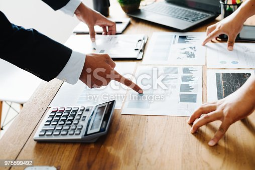 975599364istockphoto Group of Businesspeople discussing the charts and graphs,businessmen discussing on stockmarket document in office,Business partners consult documents at meeting,Concept of brainstorm teamwork planning 975599492