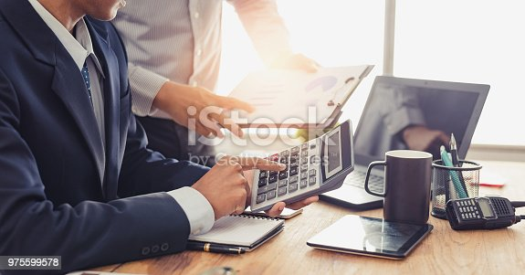 istock Group of Businesspeople discussing the charts and graphs,businessmen discussing on stockmarket document in office,Business partners consult documents at meeting,Concept of brainstorm teamwork planning 975599578