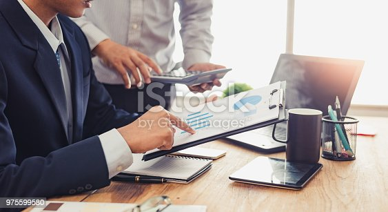 975599364istockphoto Group of Businesspeople discussing the charts and graphs,businessmen discussing on stockmarket document in office,Business partners consult documents at meeting,Concept of brainstorm teamwork planning 975599580