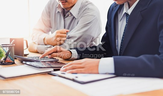 975599364istockphoto Group of Businesspeople discussing the charts and graphs,businessmen discussing on stockmarket document in office,Business partners consult documents at meeting,Concept of brainstorm teamwork planning 975599704