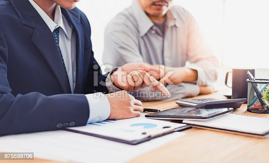 975599364istockphoto Group of Businesspeople discussing the charts and graphs,businessmen discussing on stockmarket document in office,Business partners consult documents at meeting,Concept of brainstorm teamwork planning 975599706