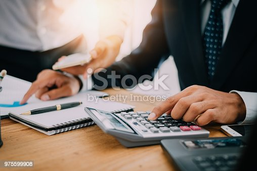 975599364istockphoto Group of Businesspeople discussing the charts and graphs,businessmen discussing on stockmarket document in office,Business partners consult documents at meeting,Concept of brainstorm teamwork planning 975599908