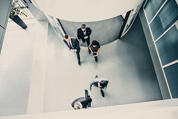 group of  businesspeople entering the lobby - entrance stock photos and pictures
