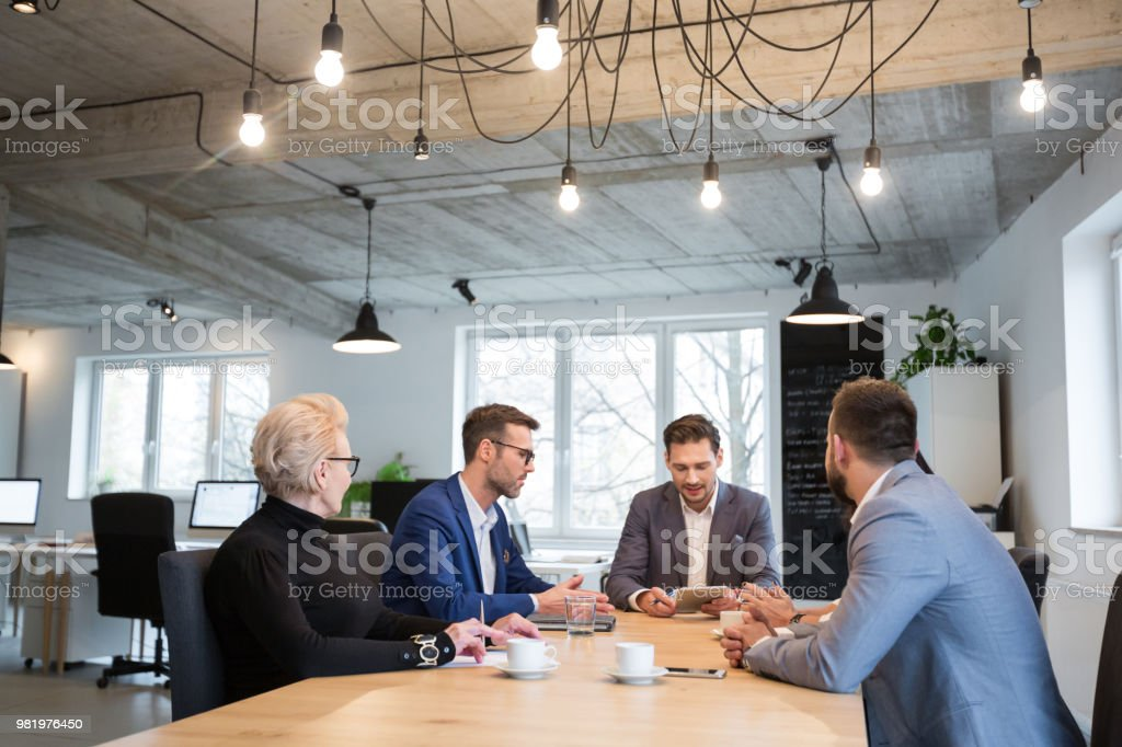 Group of businesspeople having a meeting Young businessman looking at digital tablet and talking with colleagues in office meeting room. Group of businesspeople meeting in modern office space. Active Seniors Stock Photo