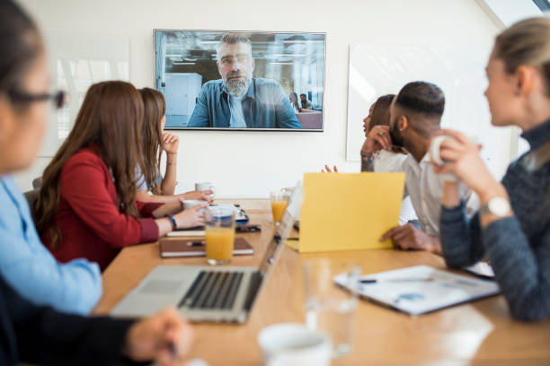 Group of businesspeople having a video conference call with their superior stock photo