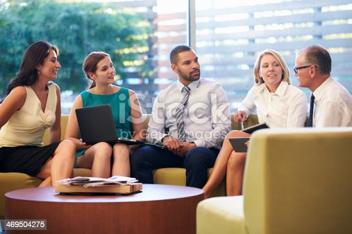 504879112istockphoto Group Of Businesspeople Having Meeting In Office Lobby 469504275