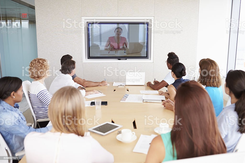 Group Of Businesspeople Having Video Conference In Boardroom stock photo