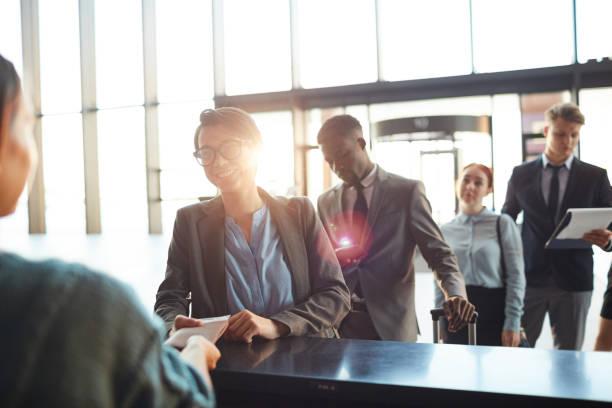Gruppe von Geschäftsleuten in Schlange an Schalter am Flughafen – Foto
