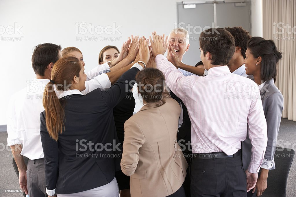 Group Of Businesspeople Joining Hands In Circle At Company Semin stock photo